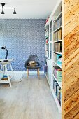 Bücherwand und Armlehnstuhl vor blau-weiß tapezierter Wand