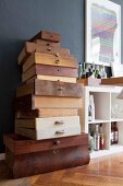 Vintage wooden drawers stacked against dark grey wall next to white open-fronted shelves