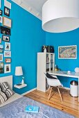 White desk and open-fronted shelves in bedroom with gallery of pictures of bright blue walls