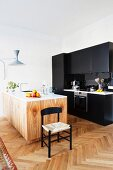 Black kitchen counter and pale, wood-grained island counter in renovated period apartment