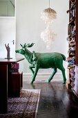 Green stag sculpture below capiz-shell lamp in living room