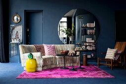 Hot-pink rug and large round mirror in dark blue living room