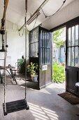 Swing in front of open industrial door with view of courtyard