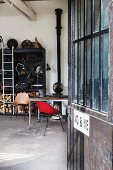 View into workshop interior with vintage stove and black shelving