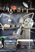 Various lamps and vintage typewriter on black shelves