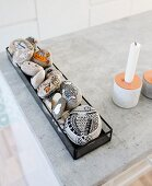 Pebbles painted with fish motifs in glass tray next to candlestick on concrete surface