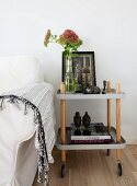 Antique picture, sedum in glass vase and ethnic ornaments on serving trolley next to white loose-covered sofa