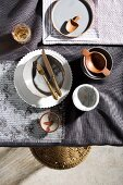 Table set in shades of grey with crockery of various types