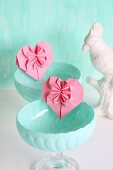 Pink origami hearts in turquoise dessert bowls