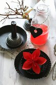Red origami flower in round tart tin and red drink in bottle
