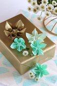 Origamisterne auf einem golden verpackten Geschenk