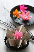 Bunte Origamiblumen aus Papier in runden Backformen