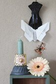 Origami butterfly held in clip above gerbera daisy and candle