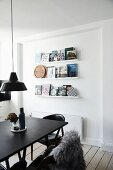 Black dining table in front of books on three narrow shelves