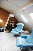 Pale blue leather armchairs and small side table in vintage attic room