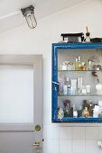 Various perfume bottles and cosmetics in vintage glass-fronted cabinet in bathroom