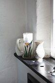 Still-life arrangement of jug and vases on windowsill