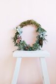 Wreath of twigs, moss and succulents leaning against wall on white wooden stool