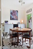 Round dining table and retro chairs on cowhide rug