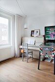 Piano and vintage chair next to colourful pinball machine