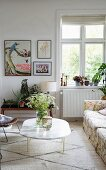 Vase of wildflowers on marble coffee table and house plants on flower stand