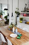 Ceramic bowls and vases of flowers on rustic table below industrial-style pendant lamps