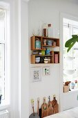 Chopping boards on floor below collection of tea caddies and glass containers on wall-mounted wooden shelves