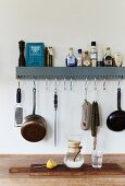 Kitchen utensils on wall-mounted shelf with hooks hung in holes