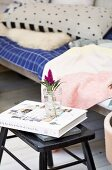 Book and flower in water glass on black stool next to comfortable wooden couch