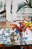 Ethnic sculpture and glass vase holding twigs of colourful leaves on coffee table