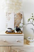 Feminine accessories on tray in front of artworks leaning against wall on top of pale wooden cabinet