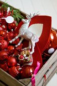 Stag figurine and red Christmas decorations in wooden crate
