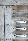 Quail eggs on three metal spoons on weathered wooden surface