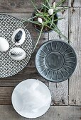 Eggs painted with feather on patterned plate and bowls on wooden surface