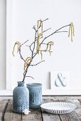 Branches of hazel catkins in vase with structured surface and matching beaker