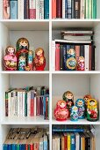 Collection of Russian dolls on bookshelves