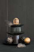Easter arrangement of feathers and painted eggs on black cake stand