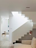 White staircase in bright, open-plan apartment