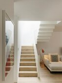 White staircase and recamier in bright interior