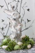 Osterhase steht im Nest aus Kresse und Zuckereiern
