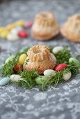 Miniature bundt cakes in nests of cress and colourful sugar eggs