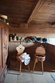 Two old farmhouse chairs in front of traditional hats on shelf