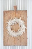 Wreath of feathers on old chopping board hung on radiator