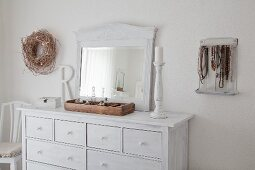 Old mirror on white-painted chest of drawers