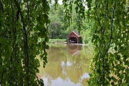 Blick durch hängende Zweige auf einen See und Bootshäuschen
