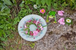 Wreath of sweet Williams, hydrangeas and grass on plate