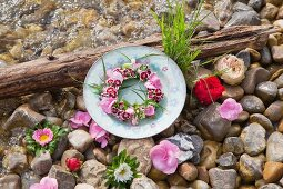 Wreath of flowers on plate and flowers on pebbles next to water