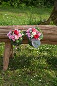 Two metal baskets filled with grass and flowers on wooden bench