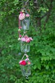 Roses and sweet Williams in three suspended vases hung from tree