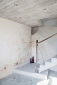 Concrete staircase with steel balustrade and concrete and brick walls